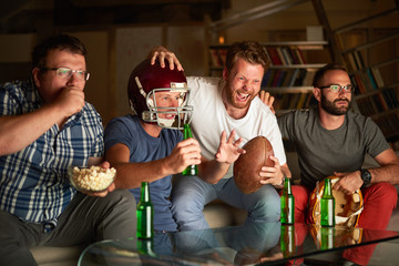 Four friends watching game of american football on television