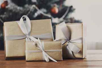 Christmas gifts on decorated tree background, holiday concept