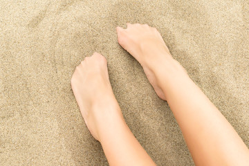 Female toes covered with sand against sandy pattern on background