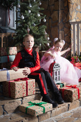 Boy and girl on the porch opening gifts
