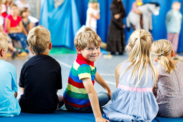 Children watching theater or concert at school. Little kid boy smiling