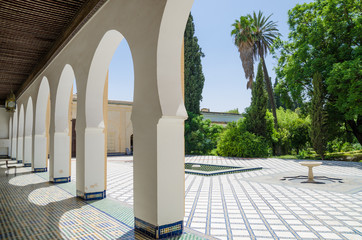 Beautiful white arches of arabic building with lush green garden in Marrakesh, Morocco, North Africa