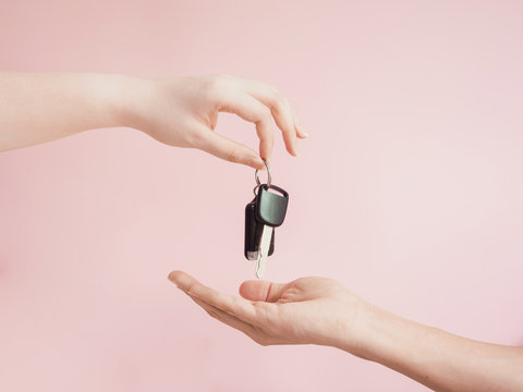 asian woman give her  car key to new car owner by beauty finger and hand with pink pastel background
