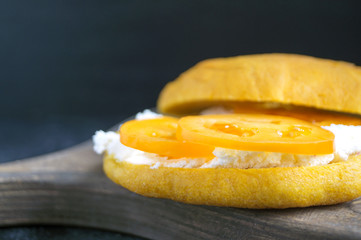 Yellow bun with tomatoes and soft cheese.