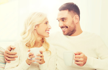 happy couple with cups drinking tea at home