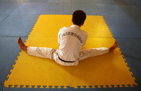 A man stretches before a martial arts class at the Karate Club at Peshawar stadium in Peshawar
