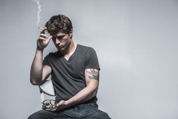 Stressful guy smoking and thinking about problems