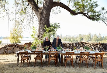 Senior couple setting the table for a Farm To Table dinner party at their home