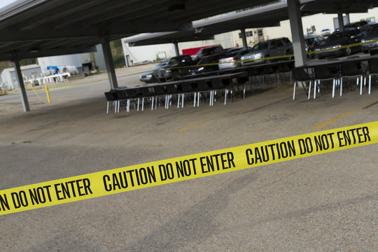 Yellow caution tape warning do not enter across the image in front of tables and chairs set up under a carport for an outdoor event.
