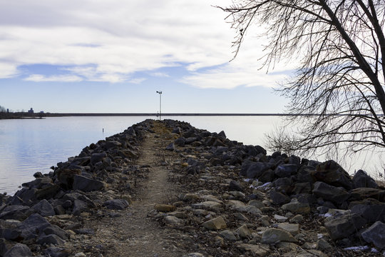 A wide view of a still lake from the top of a manmade retaining wall covered with large limestone boulders and sand.