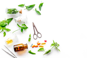 Harvest medicinal herb. Leaves, bottles and sciccors on white background top view copyspace