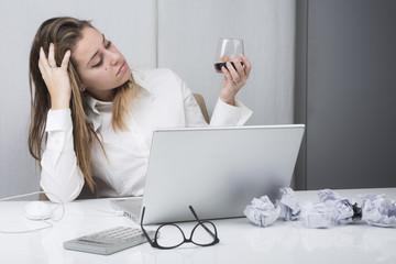 Manager disperata,seduta alla sua scrivania guarda il bicchiere di vino.
