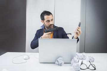 Manager seduto nella sua scrivania vestito con giacca camicia e cravatta arancione punta una pistola alla suo cellulare