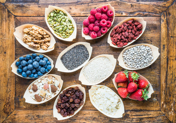 Super food fruits, berries, nuts, seeds top view on rustic wood background. Detox, superfood concept.