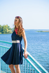 Portrait nice middle age thin woman in american pin up style. Lady in deep blue polka dot dress, red sunglasses and scarf