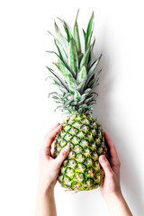 Tropical fruits background. Hand hold pinneapple on white top view copyspace