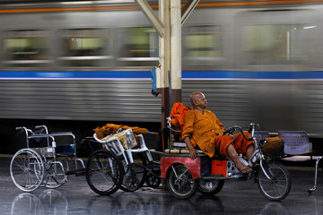 A Buddhist monk sits on a three wheel cart with two wheel chairs behind it as he waits at Hua Lampong central station in Bangkok