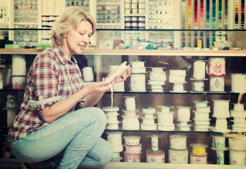 portrait of female customer standing next to different bands for sewing in shop