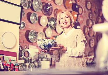 Woman buying ceramic tableware