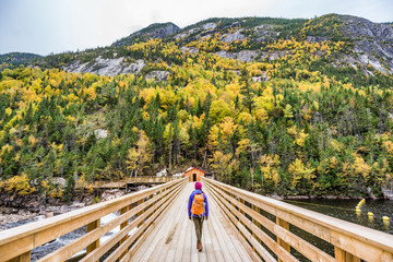 Hike woman with backpack walking in forest nature outdoors bridge. Canada travel hiking tourism at Hautes-Gorges-de-la-Riviere-Malbaie National Park. Active tourist lifestyle.