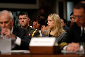 Carmen Sibayan, whose son was killed in a collision aboard the USS Fitzgerald in June, watches with her younger son as Spencer and Richardson testify during a Senate Armed Services Committee hearing on Capitol Hill in Washington