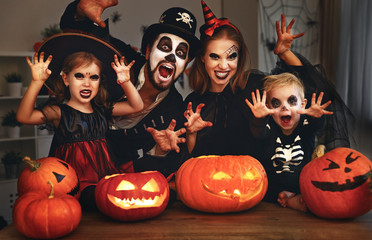 happy family mother father and children in costumes and makeup on  Halloween.