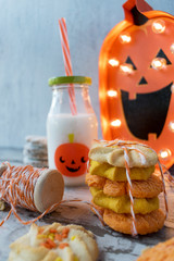 festive halloween cookies with decorations and milk