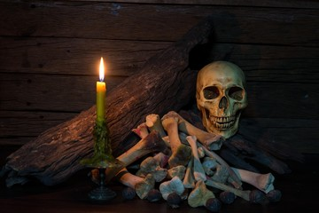 Skull on pile bone with dim light/yellow lit candle with bundle on wooden table /selective focus,