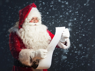 Santa Claus reading from a long list, over a dark background with snow