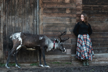 A young European girl in a plaid skirt is standing next to a reindeer near a wooden wall.