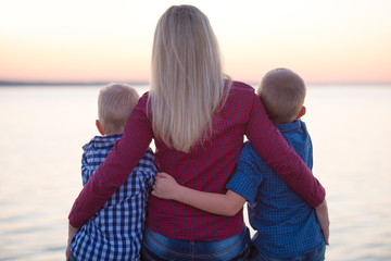 Mother and two sons sitting on the promenade and watch the sunset