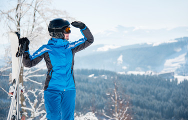 Close-up portrait of female skier with skis enjoying stunning scenery in the mountains looking away, wearing blue ski suit and black helmet copyspace