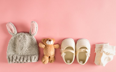 Baby clothes and accessories on a pink background