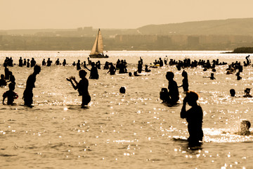 people on the beach, the city and the sailboat in the background. the hot summer day. Volga river, Saratov, Russia