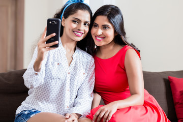 Two young happy friends making selfie pictures while sitting on sofa indoors