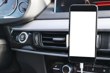 Smartphone in car use for Navigate or GPS. Driving a car with Smartphone in holder. Mobile phone with isolated white screen. Blank empty screen. Copy space. Empty space for text. modern car interior