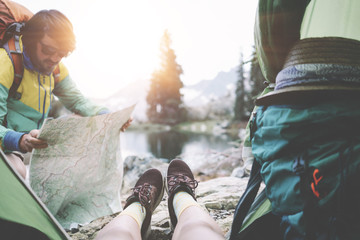 Young couple camping together in stunning mountain wilderness near the lake. POV from the tent. Woman sitting inside, man wearing sunglasses and backpack and searching for the route on map Wall mural