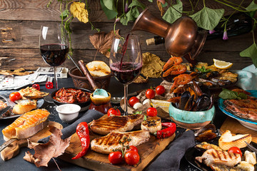 Overhead of dinner table. Assorted grilled barbecue meat and seafood with vegetable. Pork grilled steaks, salmon trout, mussels, shrimps, dried tomato, cherry tomato, chili pepper, glasses of wine.