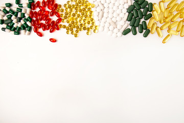 Pills background. Heap of assorted various medicine tablets and pills different colors on white background. Healthcare or medicament addiction concept. Copy space.