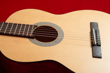 acoustic guitar on red velvet fabric, closeup object