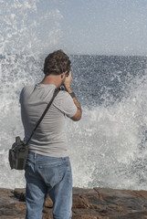 Man taking picture of surf crashing on the rocks.