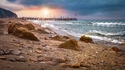 Morning sunrise in the sea with rocks on shore. Landscape of sea beach at sunrise