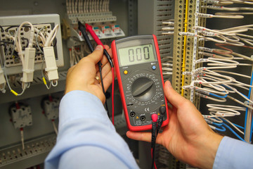 Tester in hand of electric engineer in automation panel. Adjust electric panel with multimeter