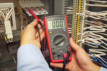 engineer tests industrial electrical circuits with multimeter in control terminal box. Engineer's hands with multimeter close-up against background of terminal rows of automation panel