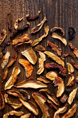 Dried forest mushrooms sliced on wooden background, top view