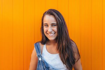 Cute Teen Girl Smiling Against Orange Background