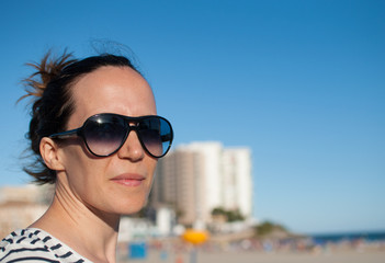 woman on the beach with big sunglasses
