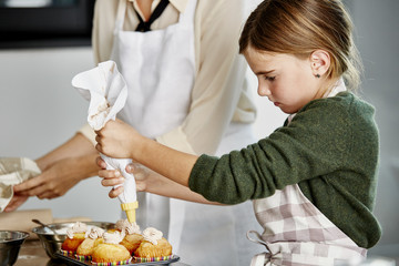 Girl Decorating Cupcakes With Icing In Kitchen