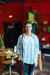 Portrait of a young businesswoman holding her briefcase standing in a creative office.