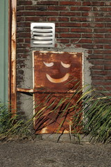 Smiley face on rusty old panel